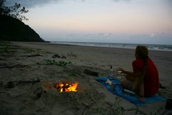 Campfire on the beach watching darkness approach